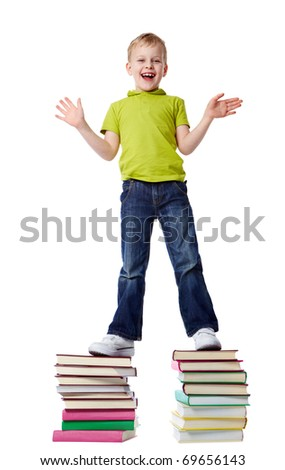 A cheerful boy standing on two heaps of books - stock photo