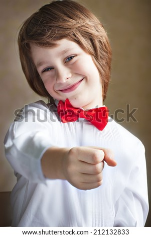 A cheerful cute smiling boy in a white shirt with a red bow-tie holding something you want (flowers, stick lolly) on a grey background closeup. Young handsome gentleman congratulating you with present - stock photo