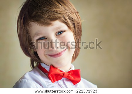 A cheerful cute smiling boy in a white shirt with a red bow-tie on grey background closeup. Young handsome gentleman congratulating somebody - stock photo