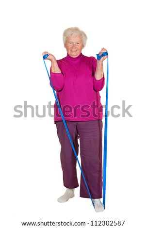 A cheerful elderly female pensioner exercises using a strap placed under her foot for leverage to strengthnen her arm and stomach muscles - stock photo