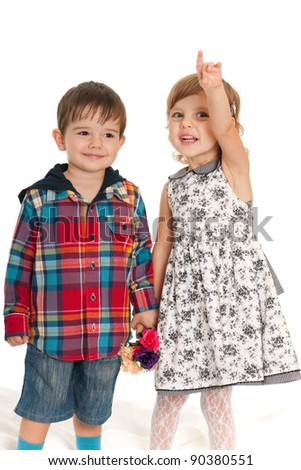 A cheerful girl and a boy are holding flowers; isolated on the white background - stock photo