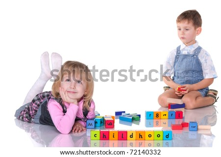 A cheerful girl and a little concentrated boy are playing blocks; isolated on the white background - stock photo