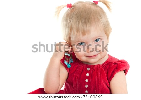 A cheerful girl dressed in a nice red dress is trying an earing; isolated on the white background - stock photo