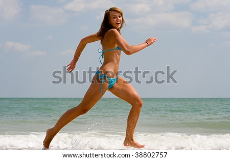 A cheerful girl running at a beach - stock photo