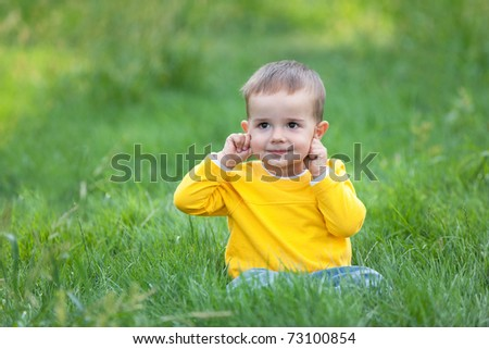 A cheerful kid is sitting on the green grass pointing his ears - stock photo
