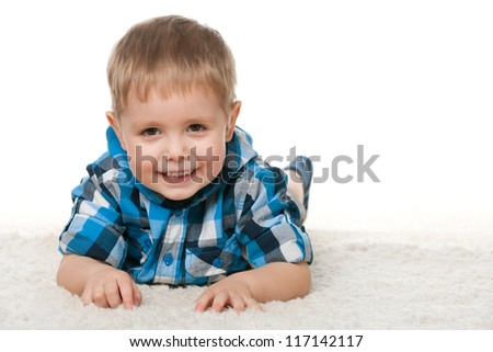 A cheerful little boy is lying on the white carpet; on the white background - stock photo