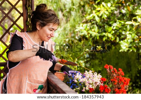 a cheerful old lady gardening in her terrace - stock photo