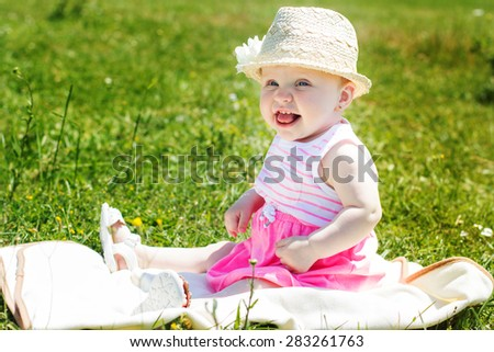 A cheerful smiling baby girl is sitting on the grass - stock photo