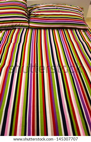 a cheerful striped bed in a domestic bedroom - stock photo
