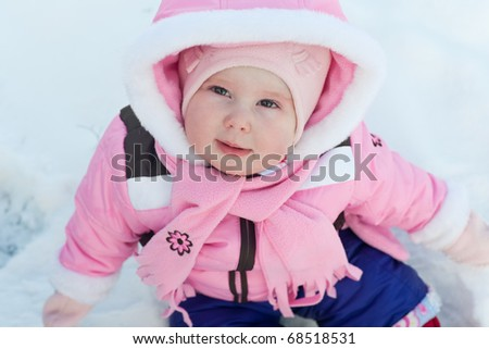 A cheerful toddler in pink walking in a winter snowy park - stock photo