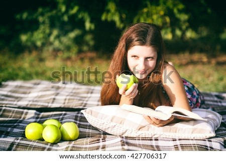 A cheerful young girl, lying on a grass in a park, eating an apple and reading a book. Sun shine in her face and she is smiling because she is happy - stock photo