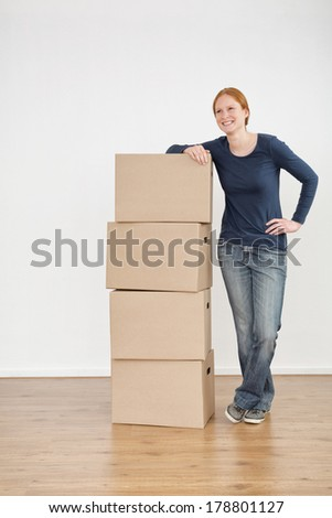 A cheerful young woman standing next to moving boxes in an empty new room. - stock photo
