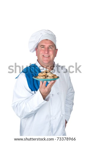 A chef holds up a plate of freshly baked cookies. - stock photo