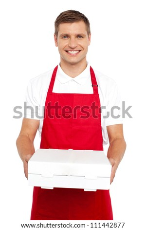 A chef in red uniform offering you a pizza box. Smiling at camera - stock photo