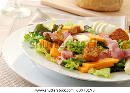 A chef's salad in a bowl next to a loaf of fresh baked bread - stock photo