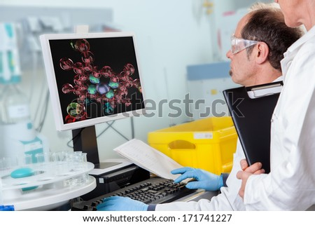 A Chemist Assistant is teached by her Professor in Atom Structure. - stock photo