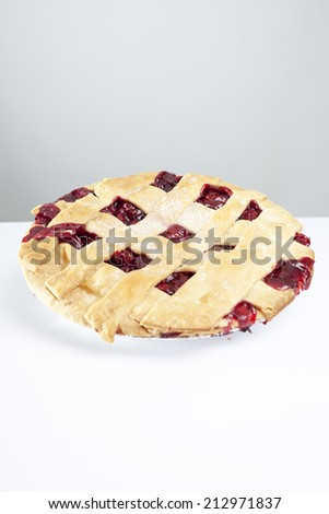 A cherry pie with overflowing filling - stock photo