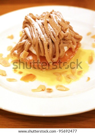 a chestnut cream cake with almond chips on a white plate - stock photo