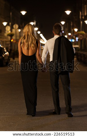 A chic woman and elegant man in a city at night - stock photo