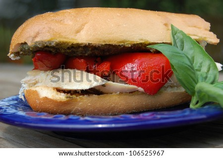 A chicken breast sandwich with roasted red peppers and pesto on a roll - stock photo