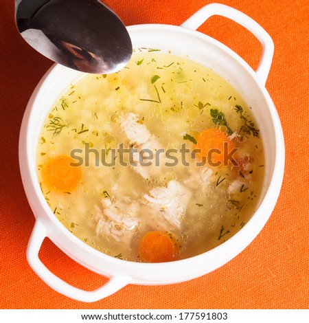A chicken broth in white ware on the orange tablecloth - stock photo