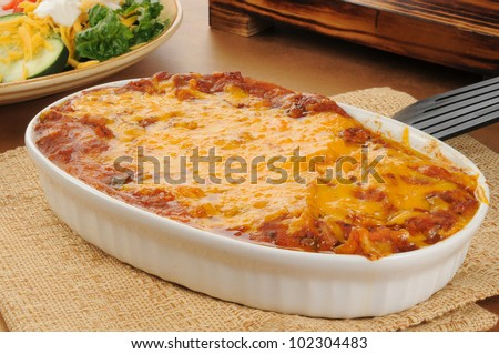 A chicken enchillada casserole topped with cheddar cheese - stock photo