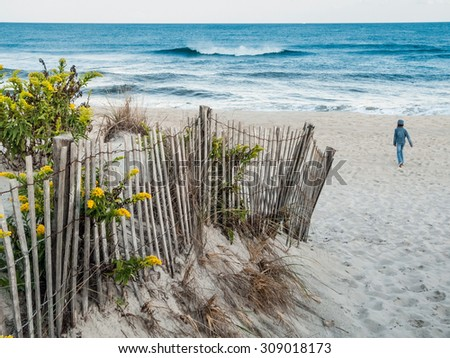 A child alone on the beach on a breezy Fall late afternoon. - stock photo
