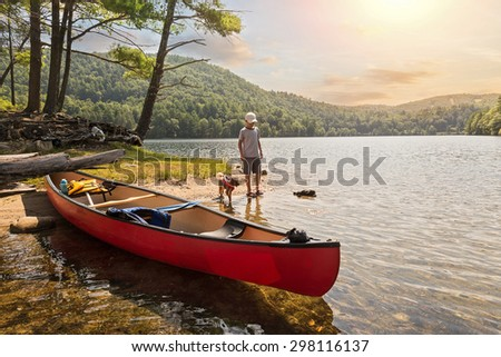 a child and his pet dog playing on the shore of a lake after canoeing during a beautiful, summer sunset - stock photo