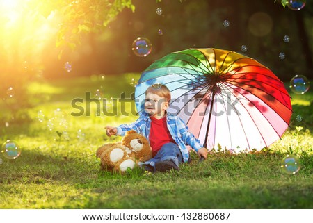 A child at sunset, back light. Kid on the meadow in the park. The baby on the background of the summer. Summer scene. Child playing with soap bubbles and rainbow umbrella - stock photo