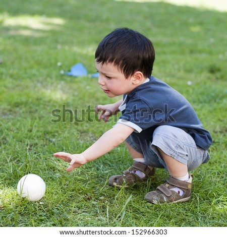 A child boy playing with a small  ball on a grass in the garden. - stock photo