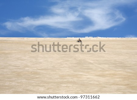 A child driving desert scooter in a desert at bahrain - stock photo