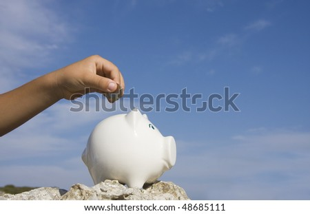 A child hand putting a euro coin on a piggy bank - stock photo
