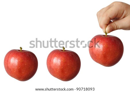 A child holds a large red apple fruit stem and wants to put him last among the other two, in isolation - stock photo