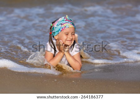 A child in a white t-shirt is in the water at the beach on a clear sunny day, his head in his hands. - stock photo