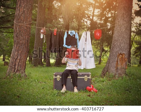 A child is reading a book with various professional uniform clothing hanging on a clothesline for a career occupation or job idea. - stock photo
