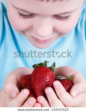 A child looks at a handful of strawberries in his hands - stock photo