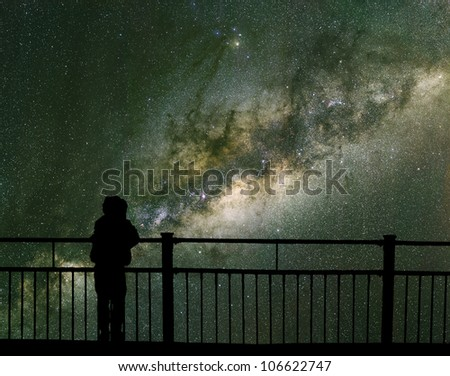 A child looks into space and the Milky way. Long exposure photograph from an astronomical observatory site. - stock photo