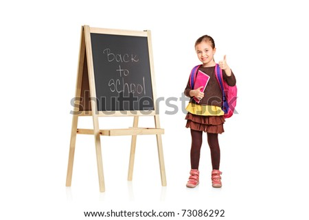 A child next to a school board holding book and showing thumb up isolated on white background - stock photo