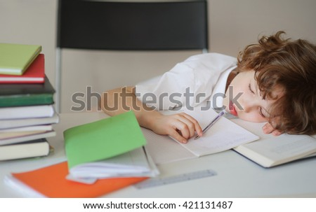 A child of primary school age do homework. The boy does his homework at his desk at home. The student / pupil has been bored on the lesson. Child fell asleep during homework.  - stock photo