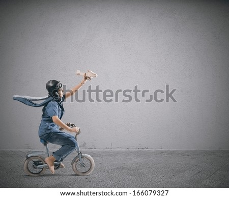A child on the bike with toy of airplane - stock photo
