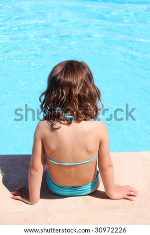 a child paddling her feet in a swimming pool exposed to the dangers of the sun without any protection - stock photo