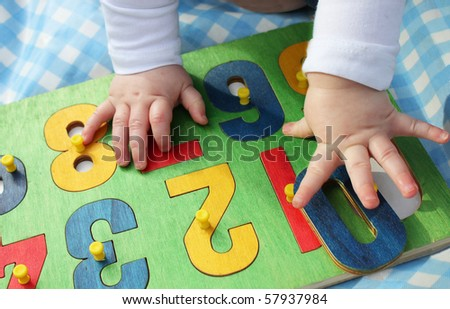 a child playing with a number puzzle - stock photo