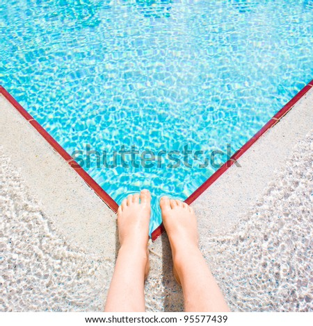 A child's feet at the edge of a bright blue swimming pool - stock photo