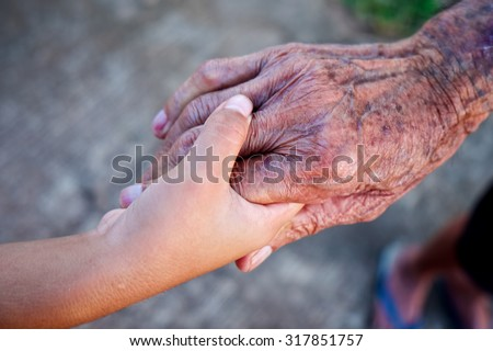A child's hand holding the hand of an old man. - stock photo