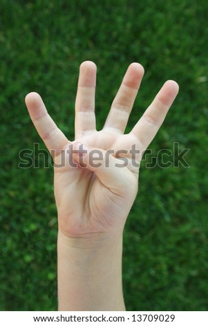 A child's hand holding up four fingers demonstrating the number four - stock photo