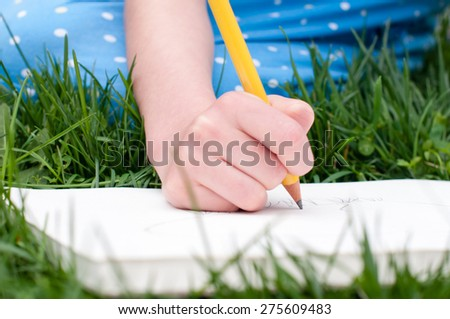 A child's hand holds a yellow pencil and draws in a sketchbook.  The child is sitting in the grass and her blue dress is visible in the background - stock photo