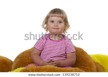 A child sits on a soft toy on a white background - stock photo