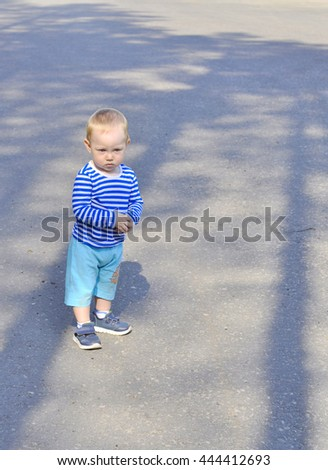 A child stands in the shade of pine trees on a background of asphalt. - stock photo