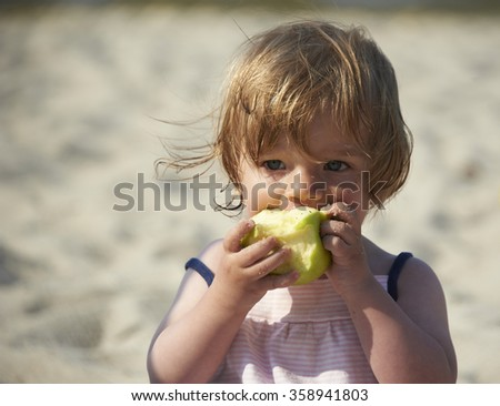 A child toddler baby girl one year old eating apple at the sandy beach summer time, background sea, portrait - stock photo