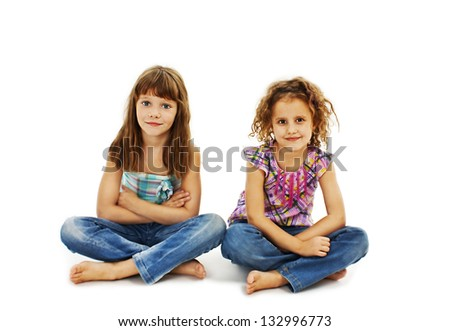 A child, two girls sitting on the floor. Isolated on white background - stock photo